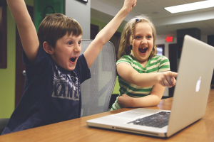 boy and girl at a computer happy